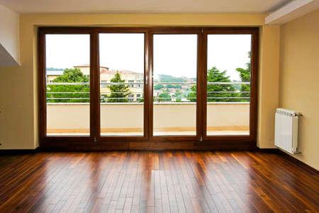 wood flooring: Four glass doors in empty living room