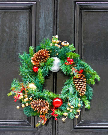 Conifer Christmas wreath with pine cones at door photo