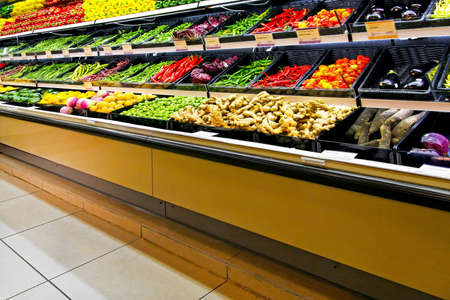 Long shelf in supermarket with fresh vegetables photo