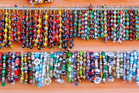 Row of necklaces and bracelets made of Murano glass photo