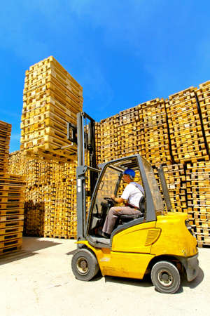 Man operating forklift lifting bunch of euro pallets  Banque d'images