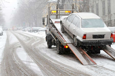 Car break down and towing at snow street Фото со стока
