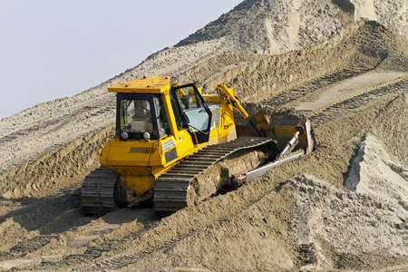 Bulldozer with track move sand at construction site