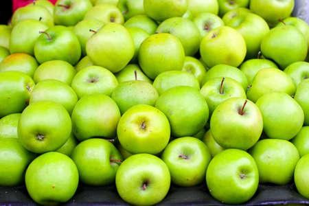 Big pile of organic green apples on market