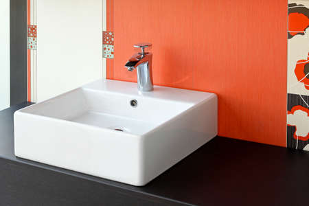 Modern square bathroom sink and red wall Stock Photo - 13979393