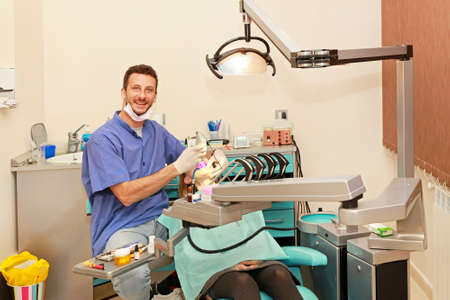Smiley doctor and girl in dentist office photo