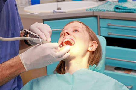 Bloonde chica joven en silla de dentista oficina