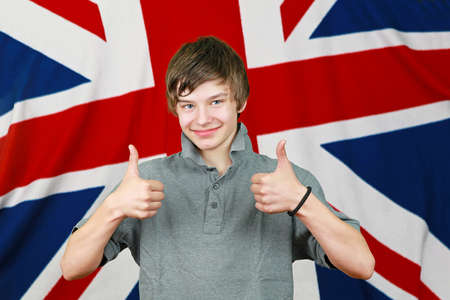 Young British boy with thumbs up in front of Union Jack flag photo