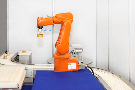 orange industry: Robotic arm at automated factory production line
