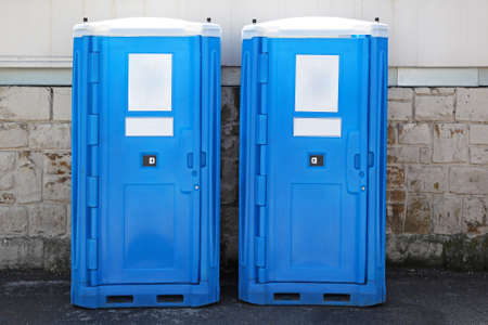 cabins: Two blue portable toilet cabins at construction site Stock Photo