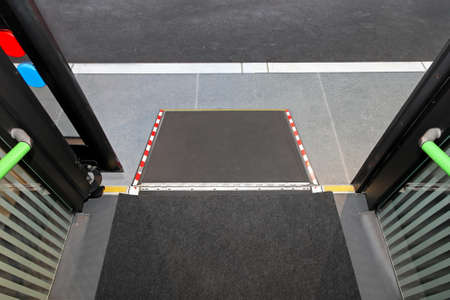 wheelchair access: Retractable ramp for wheelchair at city bus Stock Photo