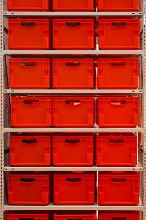 ウェアハウス内の赤いプラスチックの箱が付いている棚