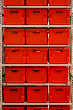 Shelf with red plastic crates in warehouse photo
