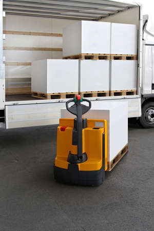 Forklift truck loading pallets of paper in lorry