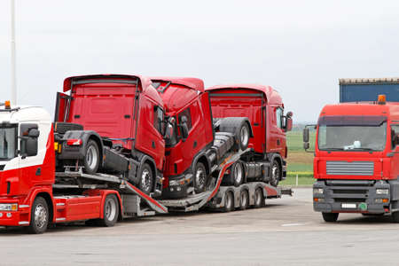 Transporting new red semi trucks at lorry