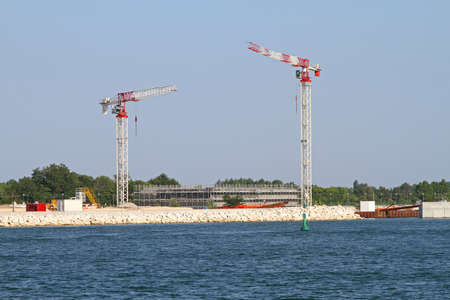 Two cranes at construction site of sea wall in Venice lagoon Stock Photo - 15174442