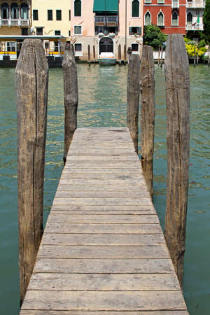 Wooden pier with old columns in Venice canal photo