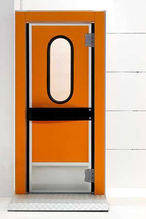 insulate: Insulated orange door at industrial fridge reefer