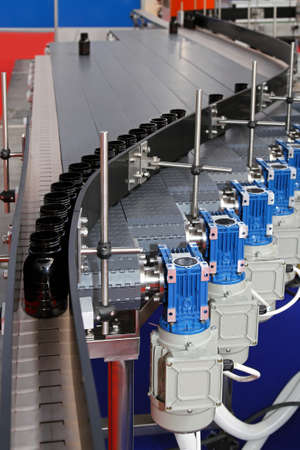 Automated conveyor belt with bottles at production line Stock Photo