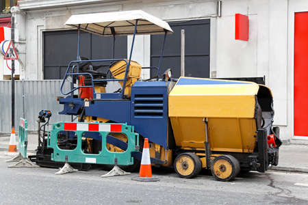 Asphalt surfacing and paving machine at street photo