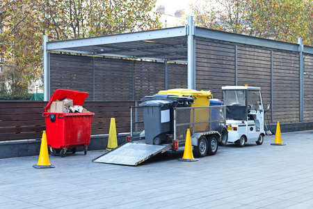 collectors: Electric vehicle with trailer for collecting garbage Stock Photo