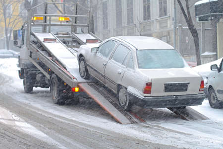 tow: Car breakdown and towing assistance at snowy day