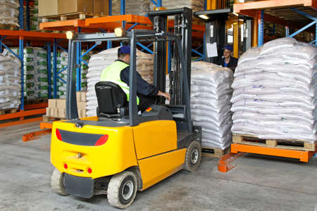 Forklift driver handling goods in distribution warehouse photo