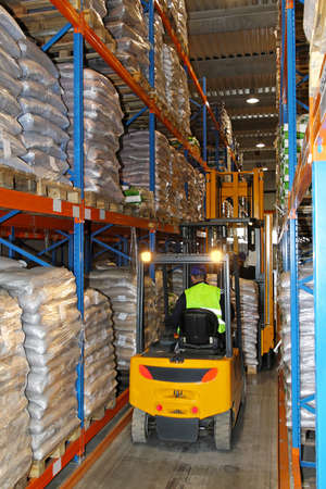 Yellow forklift in warehouse between racks photo