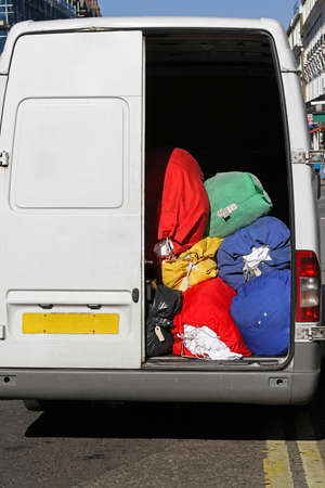 delivery service: Laundry cleaning service delivery van with bags Stock Photo