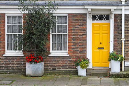 victorian architecture: Old English house with brick wall and yellow door