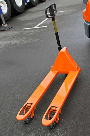 Orange manual pallet jack  truck for transport photo