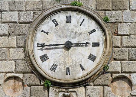 Stone clock at medieval tower in Kotor photo