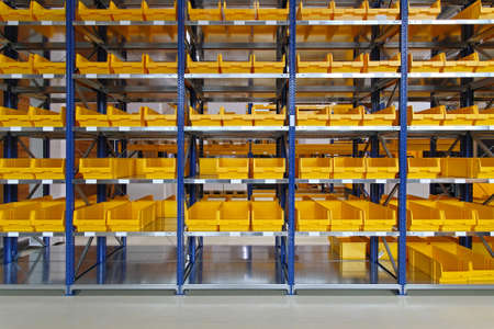storage bin: Yellow plastic bin trays at shelf in warehouse Stock Photo