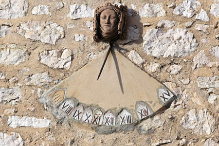 sundial: Sundial clock with Roman numbers at south wall Stock Photo