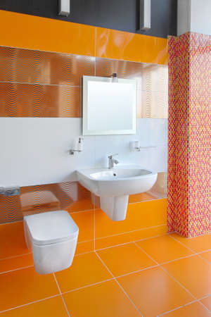 Contemporary bathroom interior with bright orange tiles photo
