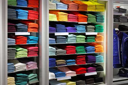 kledingwinkel: Diverse kleur shirts op plank in de winkel