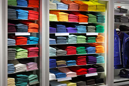 clothing store: Various colour shirts at shelf in shop