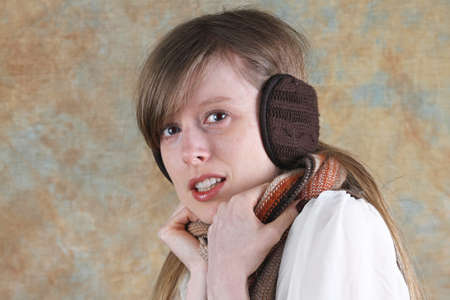 Blonde girl at cold with knitted brown earmuffs photo