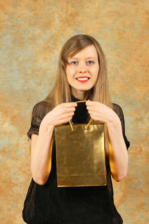 Blonde girl holding luxury golden shopping bag Stock Photo - 17036835