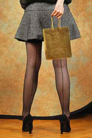 pantimedias: Bolsa de la compra de oro y sus largas piernas con medias clásicas Foto de archivo