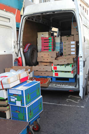 Boxes and crates of food in back of delivery van