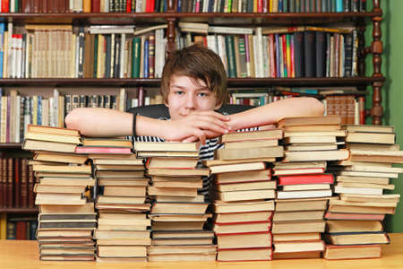 school library: Young teenage boy behind big pile of books in library