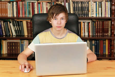 Teenage boy at desk with notebook computer in library Stock Photo - 17052971