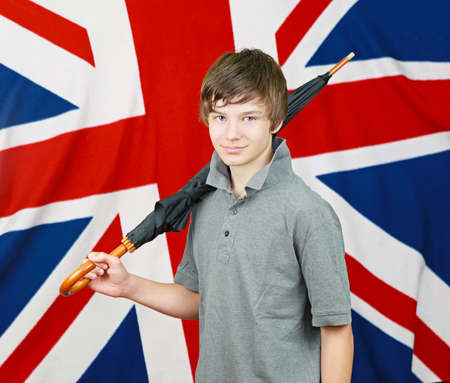 Young British boy with umbrella in front of Union Jack  flag photo