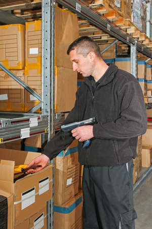 Worker with portable barcode scanner in warehouse photo