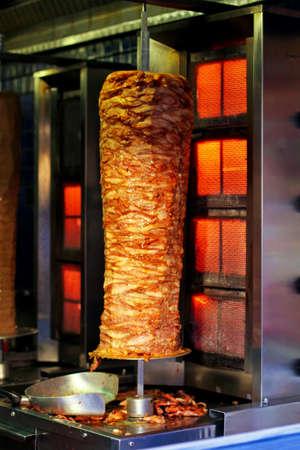 gyros: Aligned meat on metal stick roasting on street vendor Stock Photo