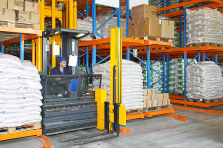 High rack stacker forklift between rows in warehouse photo