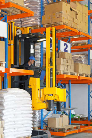 Forklift stacker between rows of goods in warehouse Stock Photo - 17194111