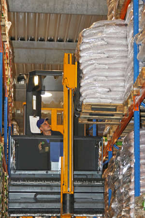 Loading goods with forklift in warehouse shelves photo