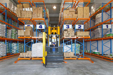 Distribution warehouse with high rack stacker forklift